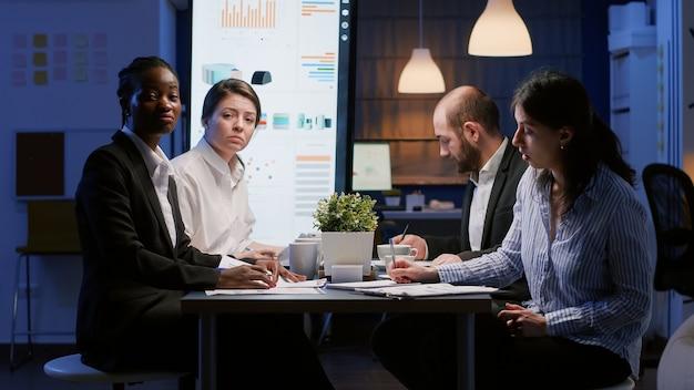 Standpunkt verschiedener geschäftsleute, die die unternehmensstrategie analysieren und unternehmensstatistiken während einer online-videokonferenz diskutieren. multiethnische teamarbeit, die in besprechungsräumen brainstorming-ideen arbeitet
