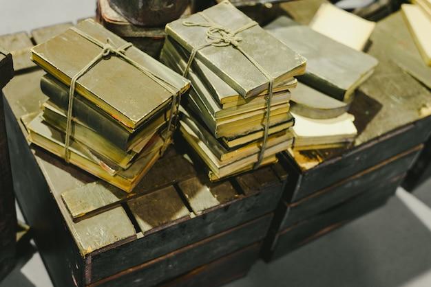 Stapel alte bücher gespeichert in verfall auf einem alten weinlesekofferraum.