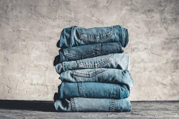 Stapel blue jeans auf grauem hintergrund
