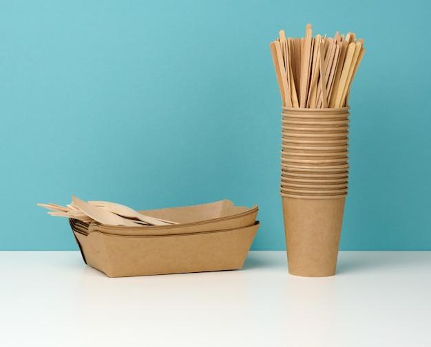 Stapel brauner einweg-pappbecher auf einem weißen tisch, holzgabeln und messer, blauer hintergrund. utensilien für getränke zum mitnehmen, zero waste