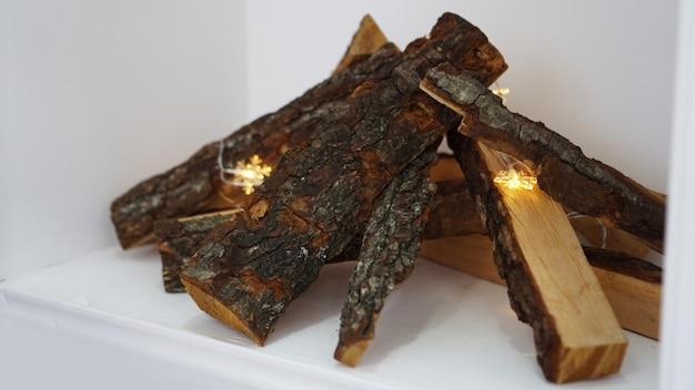 Stapel brennholz und girlande auf hellem hintergrund, nahaufnahme auf weiß