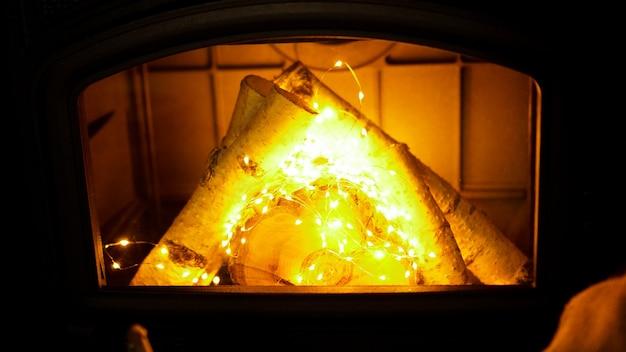Stapel brennholz und girlande auf hellem hintergrund, nahaufnahme - weihnachtszeit