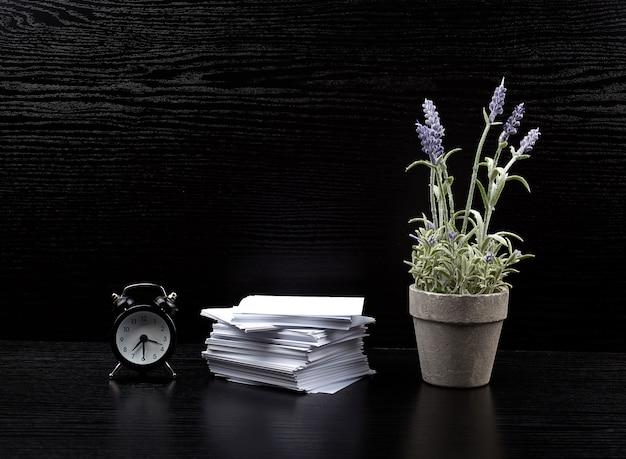 Stapel briefpapiere des weißen quadrats, ein keramiktopf lavendel und ein wecker