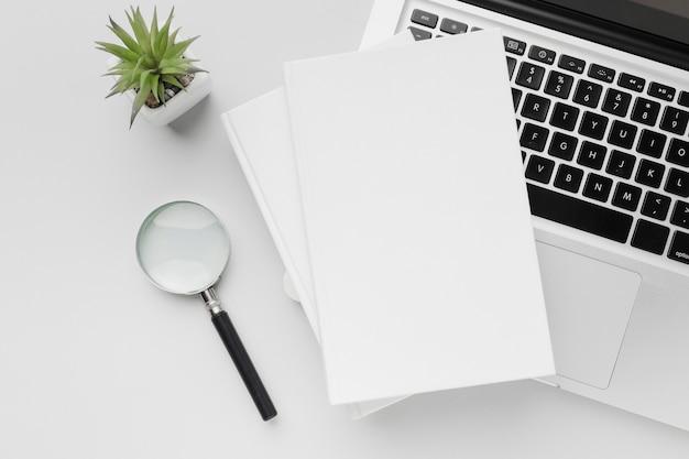 Stapel bücher auf dem schreibtisch mit laptop daneben