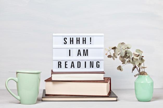 Stapel bücher, leuchtkasten mit dem text, tasse kaffee. lesen, freizeit, studienkonzept