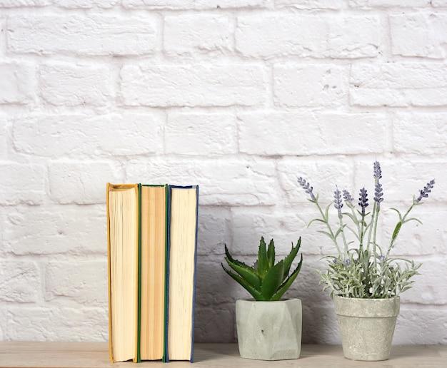 Stapel bücher und blumen in keramiktöpfen auf weißer backsteinmauer