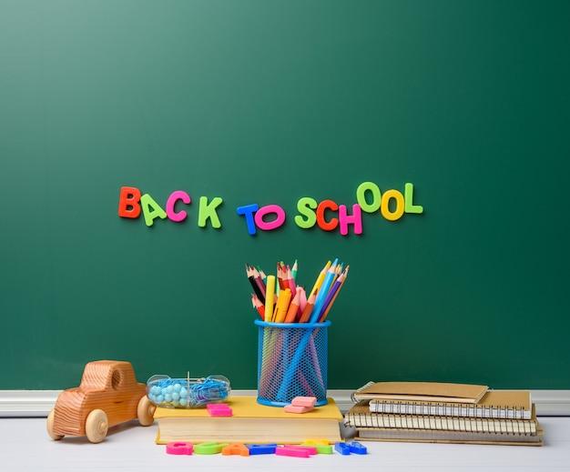 Stapel bücher und briefpapier auf leerem kalkgrünem tafelhintergrund, zurück zur schule