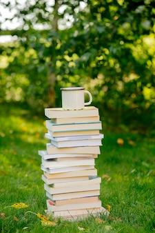 Stapel bücher und eine tasse kaffee auf dem grünen rasen im herbst