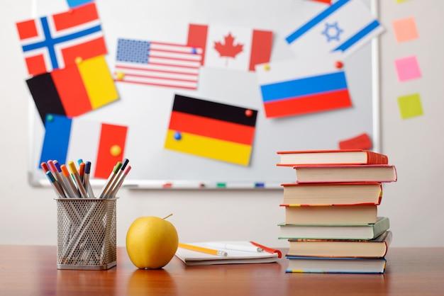 Stapel bücher vor dem whiteboard der schule mit flaggen verschiedener länder