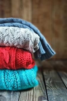 Stapel bunte gestrickte strickjacken auf hölzernem hintergrund.