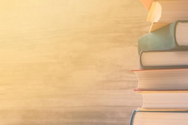Stapel bunte pastellbücher auf einem regal in der bibliothek. sonnenstrahlen fallen durch das fenster auf die bücher. bildungskonzept. zurück zu schulhintergrund.