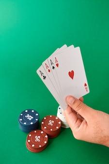 Stapel chips und hand mit vier assen, pokertuch, kartenspiel, pokerhand und chips. hintergrund.