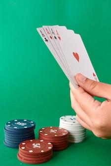 Stapel chips und hand mit vier assen, pokertuch, kartenspiel, pokerhand und chips.