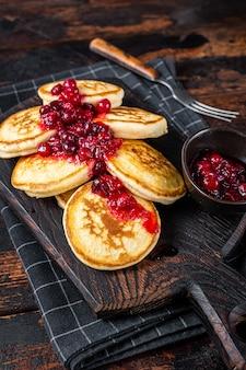 Stapel cranberry-sirup-pfannkuchen auf holzbrett. dunkler hölzerner hintergrund. ansicht von oben.