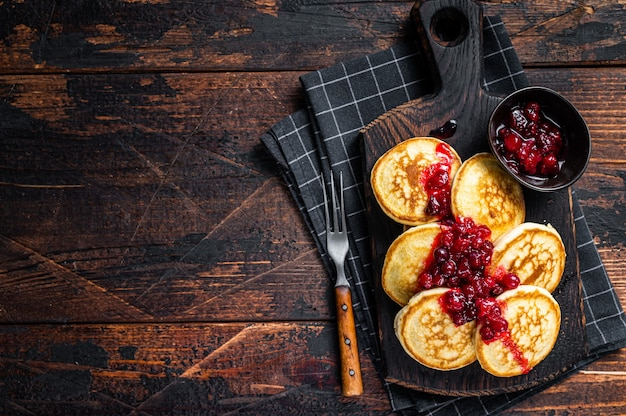 Stapel cranberry-sirup-pfannkuchen auf holzbrett