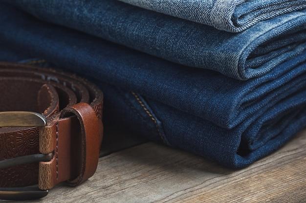 Stapel der blauen jeans und des braunen echtledergürtels auf hölzernem hintergrund
