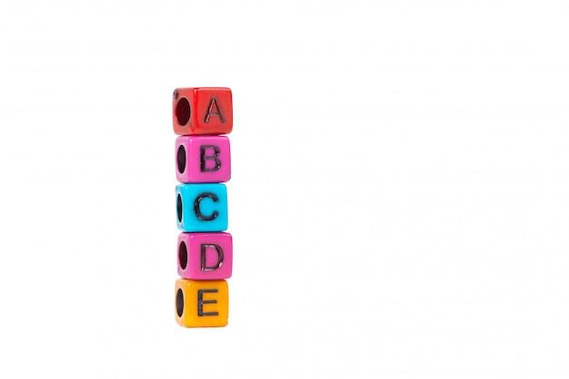 Stapel der buchstabeperle oder -perlen mit alphabet abcde auf weißem hintergrund.