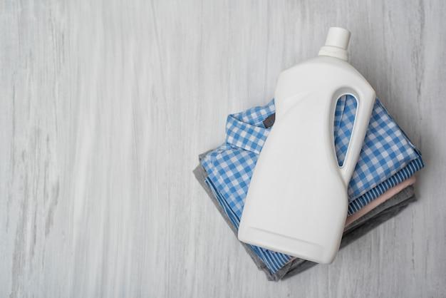 Stapel der gefalteten kleidung und der reinigungsmittelflasche. ansicht von oben