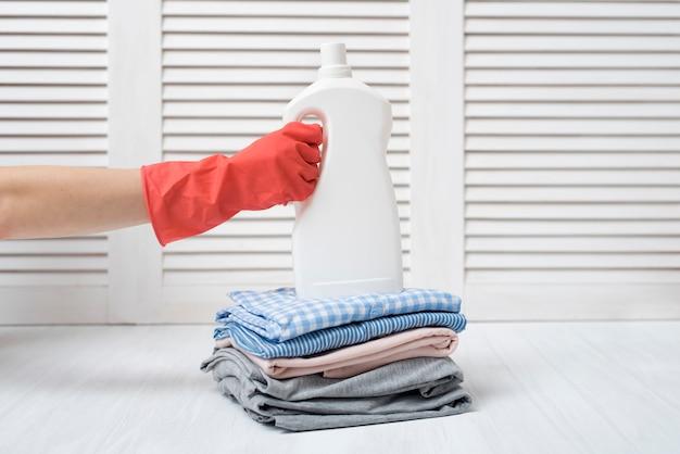 Stapel der gefalteten kleidung und der reinigungsmittelflasche in der weiblichen hand. hausarbeit