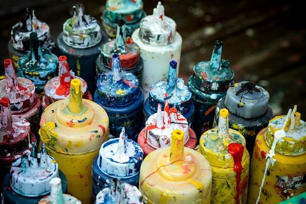 Stapel der grungy ölfarbfarbenflasche auf tabelle