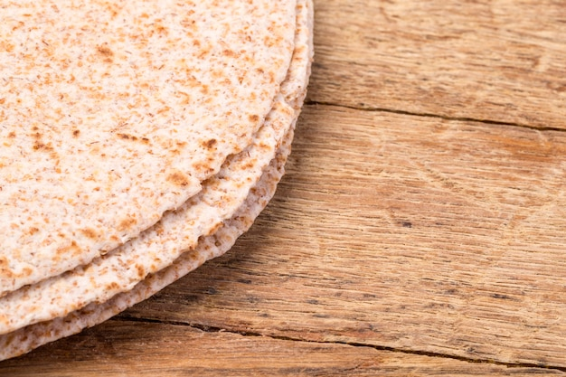 Stapel der hausgemachten vollkornmehl-tortilla auf hölzernem tischhintergrund