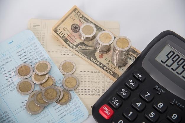 Stapel der münzendollarwährung und des geschäftsbuches mit taschenrechner