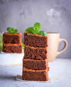 Stapel der quadratischen scheiben des gebackenen schokoladenkuchens