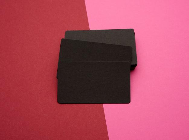 Stapel der rechteckigen schwarzen visitenkarten des schwarzen papiers auf rosa rotem raum