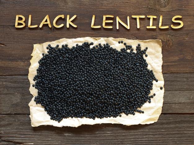 Stapel der schwarzen linsen mit einem hölzernen wort auf holz, draufsicht
