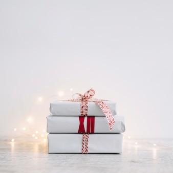 Stapel der weißen geschenkboxen mit girlande auf tabelle