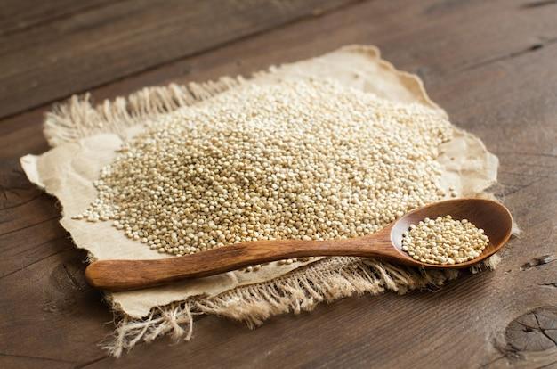 Stapel der weißen quinoa mit einem löffel auf einem holztisch schließen oben