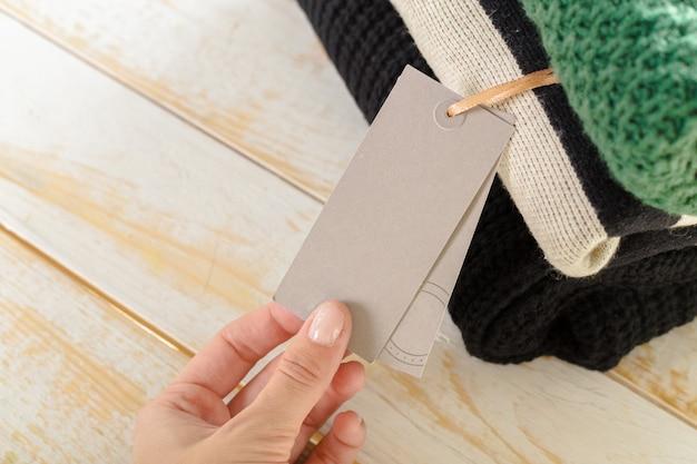 Stapel der wolle strickte warme strickjacke und des weißen aufklebers für text