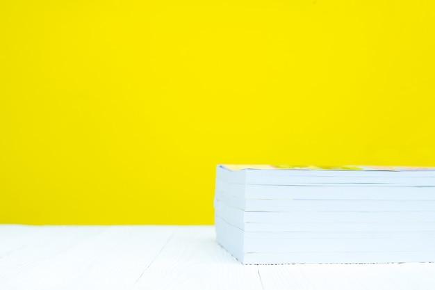 Stapel des buches auf weißer tabelle mit gelbem hintergrund.
