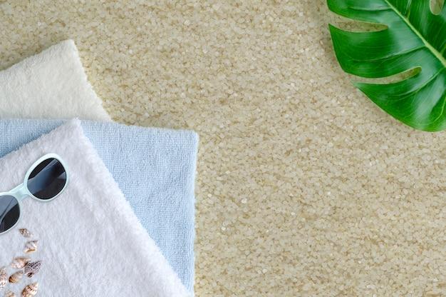 Stapel des gefalteten tuches mit grünem blatt und der sonnenbrille auf dem sand