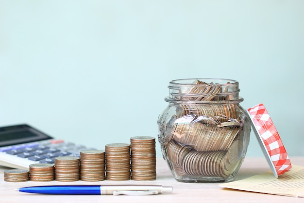 Stapel des münzengeldes und der glasflasche auf weißem hintergrund