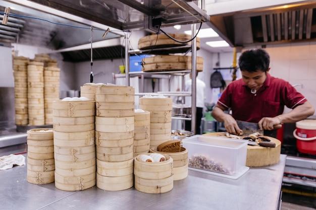 Stapel des stapelns von bambusdampfern mit dem chef, der im hintergrund kocht.