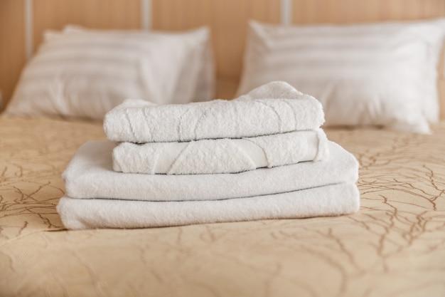 Stapel des weißen hoteltuches auf bett im schlafzimmerinnenraum.
