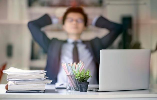 Stapel dokumente am arbeitsplatz und unschärfebild des männlichen angestellten