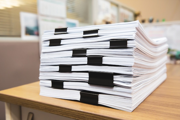 Stapel eines papierkramberichts oder eines ausdruckdokuments auf dem schreibtischstapel stapeln sich.