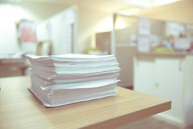 Stapel eines papiers auf dem schreibtisch gestapelt.