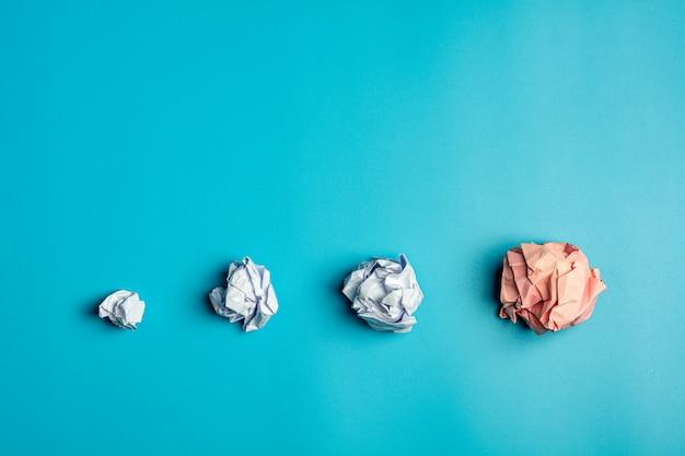 Stapel eines weiß zerknitterte papierkugeln auf blauem hintergrund.