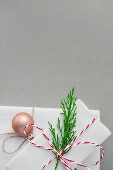 Stapel elegante weiße geschenkboxen gebunden mit roter band-grün-wacholderbusch-zweig-kugel