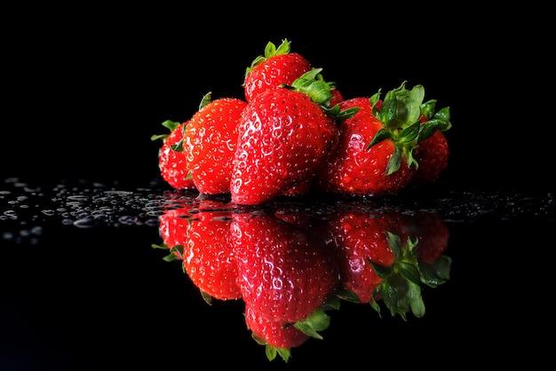 Stapel erdbeeren mit wassertropfen auf schwarzer reflektierter oberfläche und schwarzem hintergrund.