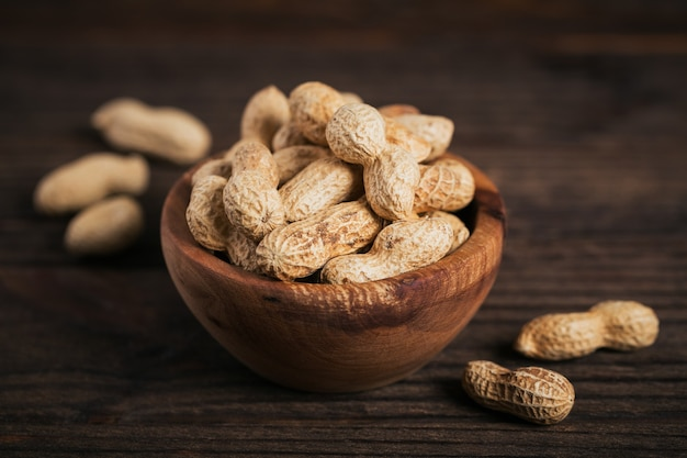 Stapel erdnüsse in einer schüssel auf einer dunklen holzoberfläche. frische nüsse in ihren schalen.