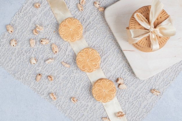 Stapel festlicher kekse und erdnüsse auf holzbrett. hochwertiges foto