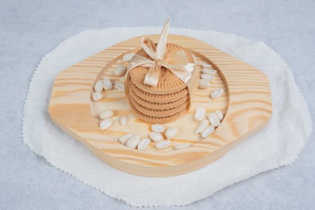 Stapel festlicher kekse und erdnüsse auf holzteller. hochwertiges foto