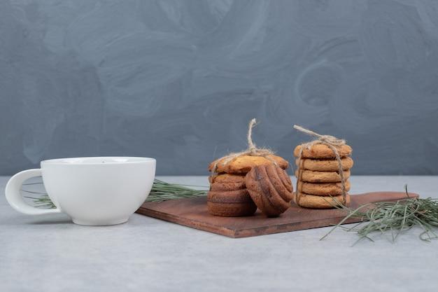 Stapel festlicher kekse und tasse tee auf grauem tisch. hochwertiges foto