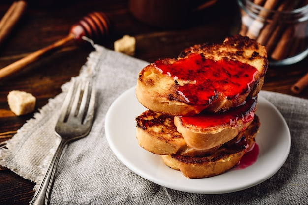 Stapel french toasts mit beerenmarmelade auf weißem teller
