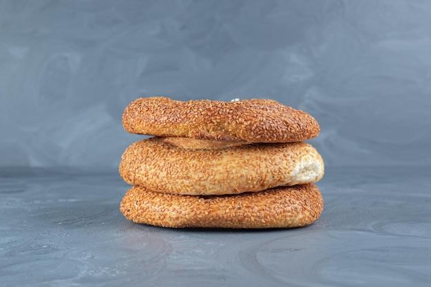 Stapel frisch gebackener bagels auf marmorhintergrund.