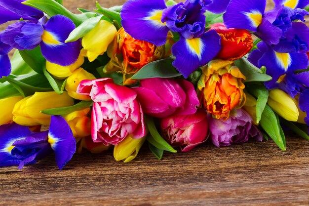 Stapel frischer frühlingstulpen und iris auf holz